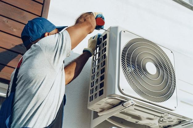 Reparateur in uniform die de buiteneenheid van airconditioner installeert