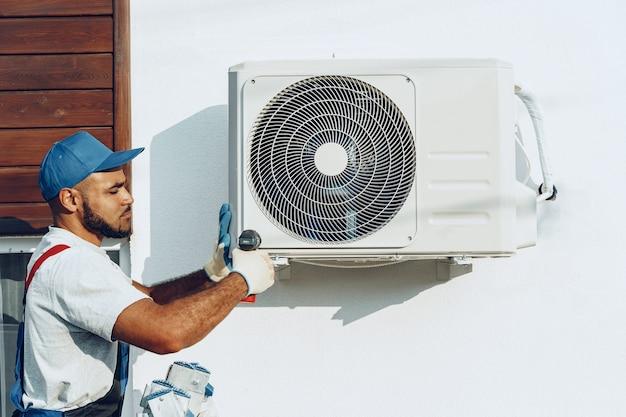 Reparateur in uniform installeren van de buiteneenheid van airconditioner