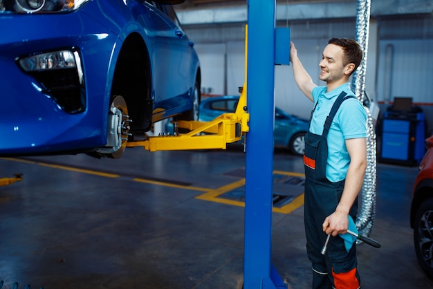 Reparateur in uniform liften voertuig op auto tankstation. automobielcontrole en inspectie, professionele diagnostiek en reparatie