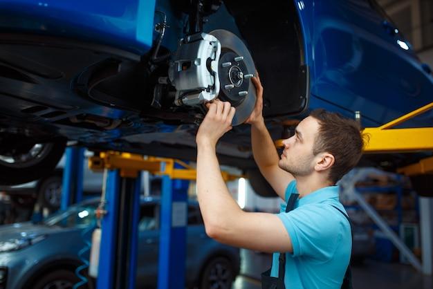 Reparateur in uniform reparatie voertuig op lift, auto servicestation. automobielcontrole en inspectie, professionele diagnostiek en reparatie