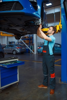 Reparateur in uniform reparatie voertuig op lift, auto servicestation. automobielcontrole en inspectie, professionele diagnostiek en reparatie