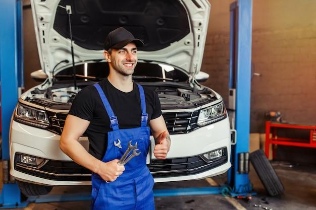 Reparateur in werkkleding die moersleutels vasthoudt en duim laat zien in de werkplaats