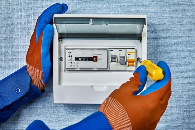 Reparateur installeerde in huis een nieuw elektrisch paneel met een elektronische elektriciteitsmeter en automatische zekeringen