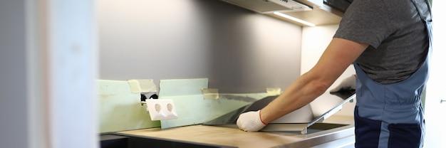 Reparateur installeert kookplaat keukentafel in appartement. installatie kookplaat in aanrechtblad. koop nieuwe keukenmeubelen en apparatuur. home apparaat installatieproces. elektrische panelen