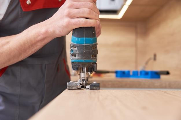 Reparateur met behulp van elektrische decoupeerzaag. zaagplaats voor inbouw van gaskookplaat in een werkblad