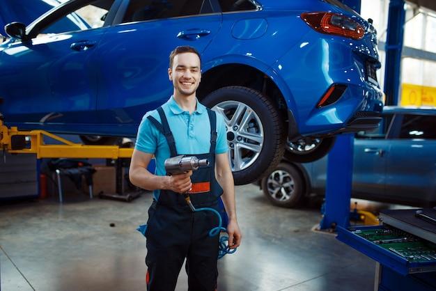 Reparateur met een controlelijst staat bij het voertuig op de lift, het autoservicestation. automobielcontrole en inspectie, professionele diagnostiek en reparatie
