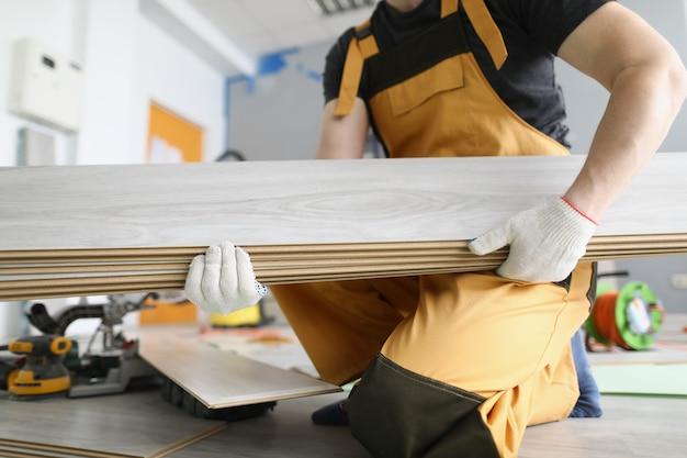 Reparateur met laminaatbord in zijn handen voor het leggen van vloerclose-up