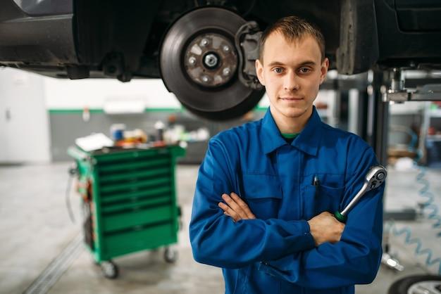 Reparateur met moersleutel tegen een auto op de lift, diagnostische opschorting.
