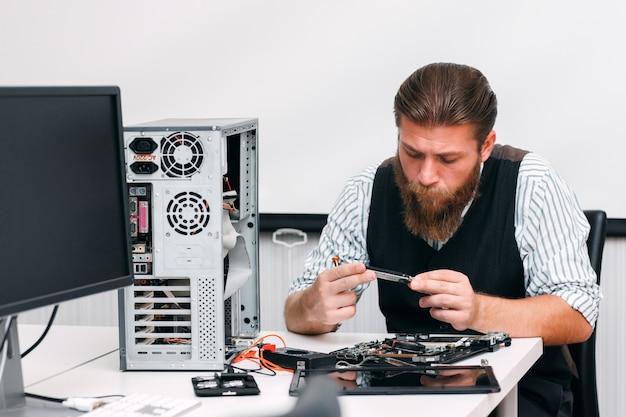 Reparateur onderzoekt binnenkant van computer. ingenieur kijken circuit van gedemonteerde cpu in reparatiewerkplaats. elektronische renovatie, reparatie, ontwikkelingsconcept
