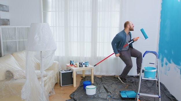 Reparateur tijdens woningbouw met rolborstel als gitaar. kerel die zingt terwijl hij huis renoveert. appartement herinrichting en woningbouw tijdens renovatie en verbetering. reparatie en decoreren.