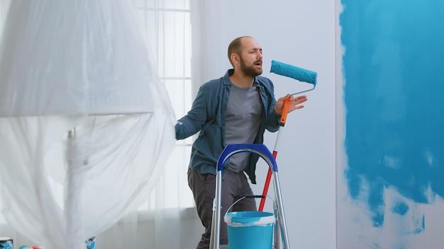 Reparateur zingt op rolborstel gedoopt in blauwe verf tijdens het opknappen van appartement. huishoudelijk werk, ontwerp, renovatie. woningbouw tijdens het renoveren en verbeteren. reparatie en decoreren.