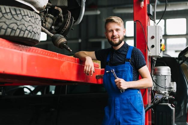 Reparateurs die op autolift leunen