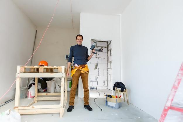 Reparatie aan huis. mannelijke handen die een elektrische perforatorboor met een boor gebruiken, maken een gat in de muur met afbladderende verf.