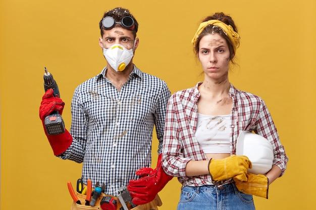 Reparatie, bouw, renovatie en huisconcept. ernstig paar dat thuis reparatie doet