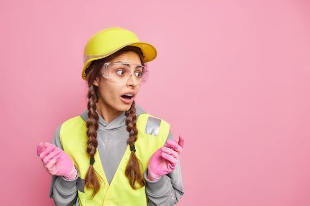 Reparatie en bouwconcept. verbaasde verraste vrouw spreidt handen kijkt weg