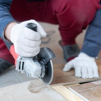 Reparatie en decoratie. een man snijdt keramische tegels met een molen.