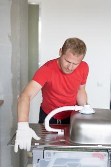 Reparatie en decoratie. meester zet de gootsteen in de keuken