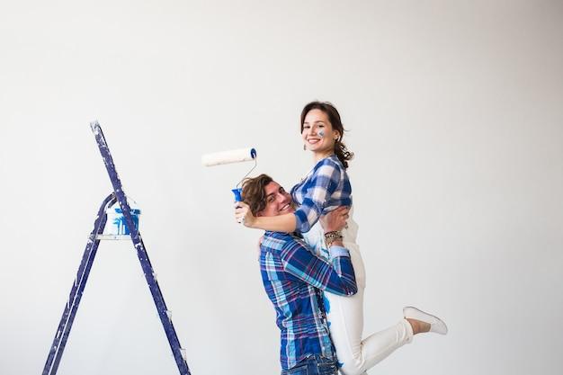 Reparatie, familie en renovatieconcept - grappige jonge vrouw en man die zich op de ladder bevinden