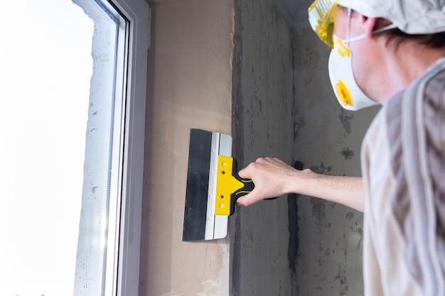 Reparatie in een appartement, raamopeningen cementeren, een mensenbouwer egaliseert de plamuur met een plamuurmes