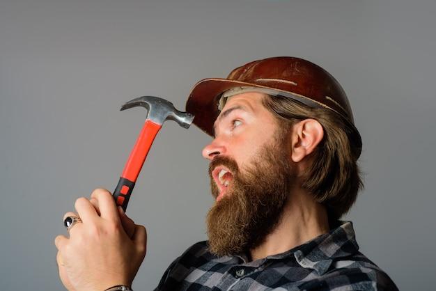 Reparatie mechanische arbeider met hamerbouwer in bouwvakkerportret van bebaarde werkman