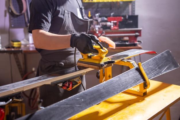 Reparatie, mensen concept - monteur, man wrijft een ski