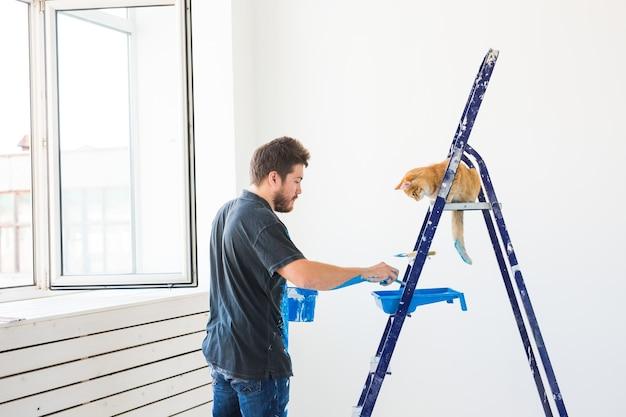 Reparatie renovatie huisdier en liefde paar concept jonge man met kat doet reparatie en schilderen muren