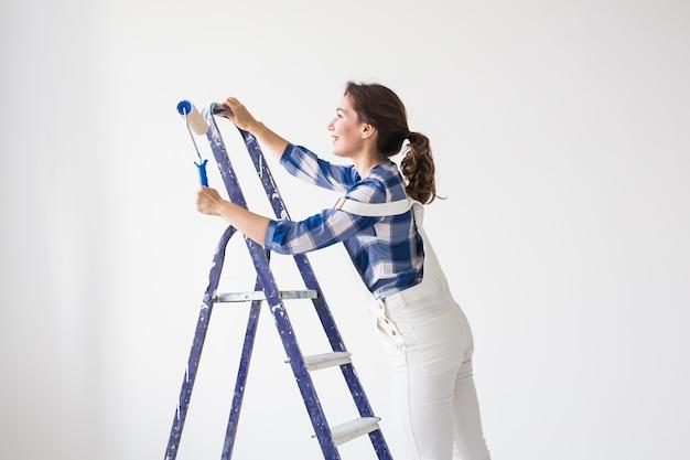 Reparatie, renovatie, nieuw huis en mensenconcept - mooie vrouw die tijdens herinrichting op de ladder staat