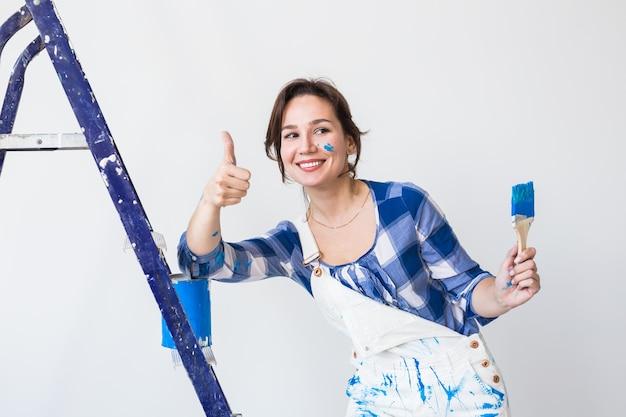 Reparatie, renovatie, werknemer en mensen concept - gelukkige jonge vrouw verf muur thuis, duimen opdagen.