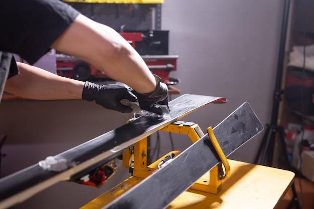 Reparatie-, service- en mensenconcept - een man die de ski repareert door een paraffine te wrijven
