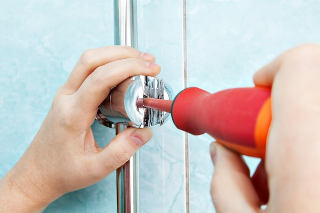 Reparatie van badkamer, close-up loodgieters hand draai schroef verstelbare douche handvat beugel met schroevendraaier.