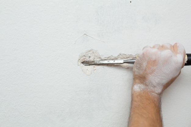 Reparatie van het pand. een man maakt een greppel om kabel in de muur te leggen.