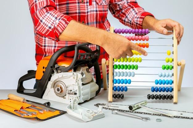 Reparatie van kettingzagen, gereedschap op benzine. reparateur die de prijs berekent.