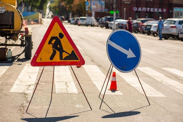 Reparatie van wegen. waarschuwingsborden over reparatiewerkzaamheden aan bestrating. aandacht omweg
