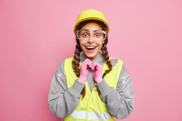 Reparatieconcept. positieve vrouw monteur draagt engineering gebouw uniform ziet er gelukkig geïsoleerd over roze muur. engineering en industriële bouw. arbeider in werkkleding