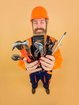 Reparatiegereedschap glimlachende werknemer houdt reparatiegereedschappen bouwindustrie technologie spanner bebaard