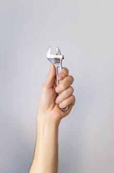 Reparatiesleutel in de handen van een mannelijke isolaat. selectieve aandacht.