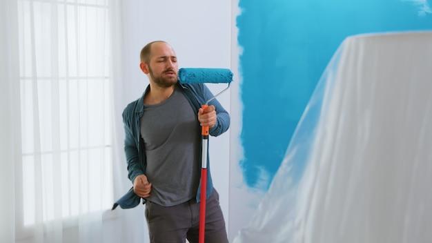 Repareer man zingen op rolborstel met blauwe verf tijdens woningrenovatie. dansen, bouwen, repareren, werken. herinrichting en woningbouw tijdens renovatie en verbetering. reparatie en deco