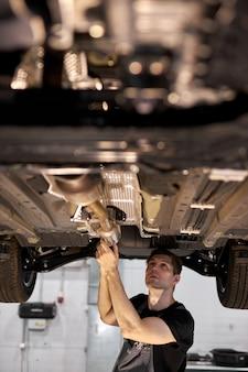 Repareren in actie. hardwerkende man werknemer in uniform werkt in de auto salon