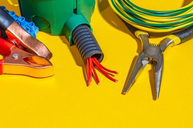 Reserveonderdelen, gereedschap en draden voor vervanging of reparatie van elektrische apparatuur op gele achtergrond