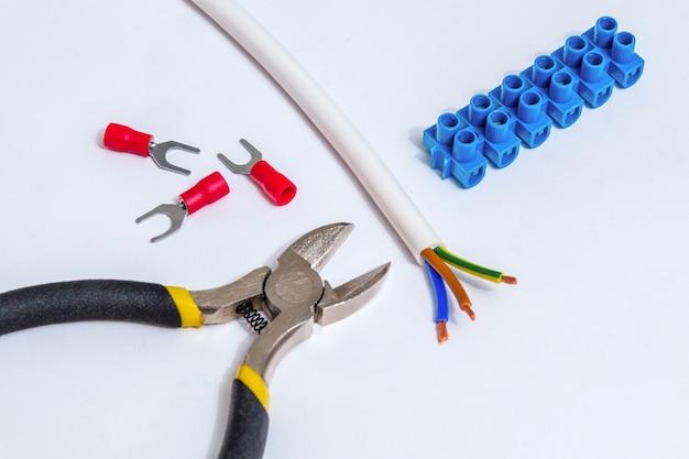 Reserveonderdelen, gereedschap en draden voor vervanging of reparatie van elektrische apparatuur op grijze achtergrond