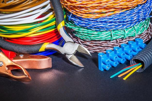 Reserveonderdelen, gereedschappen en draden op zwarte achtergrond voor elektrische reparaties of vervangingen thuis of op kantoor