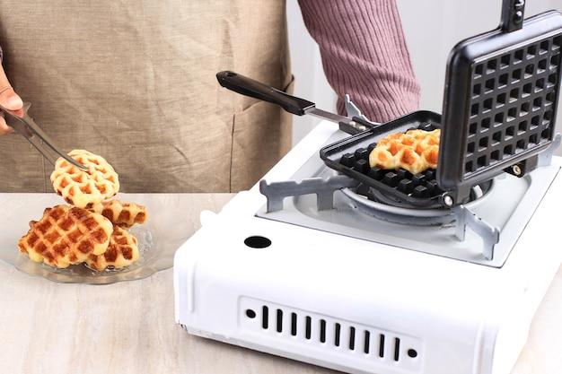 Resh gebakken croissant wafel (croffle), vrouwelijke hand zet verse croissant op bord
