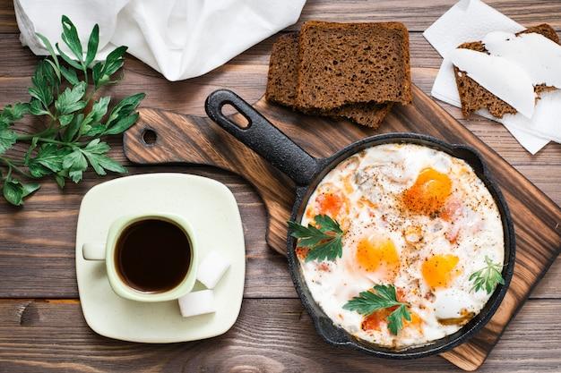 Reshakshuka van gebakken eieren met tomaten en peterselie in een pan