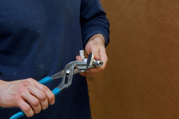 Residentiële reparatie, vervang de klep, loodgieter close-up hand sanitair tangen.