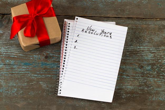 Resoluties tekst op notebookpapier met geschenkdoos voor bedrijfsconcept.