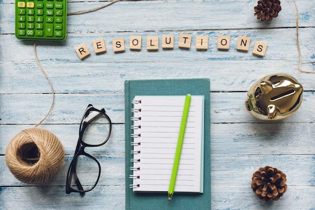 Resolutieswoord en een blocnote op lichtblauw hout