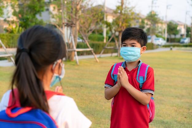 Respect betuigen is een nieuwe nieuwe begroeting om de verspreiding van het coronavirus te voorkomen. twee aziatische kinderen voorschoolse vrienden ontmoeten elkaar in school park met blote handen.
