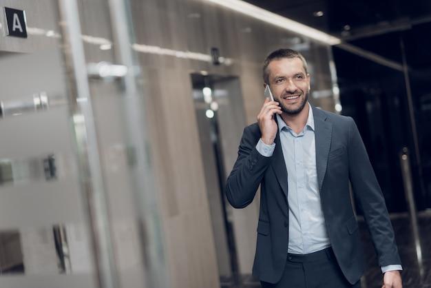 Respectabele man in strikte pak loopt langs kantoor gang