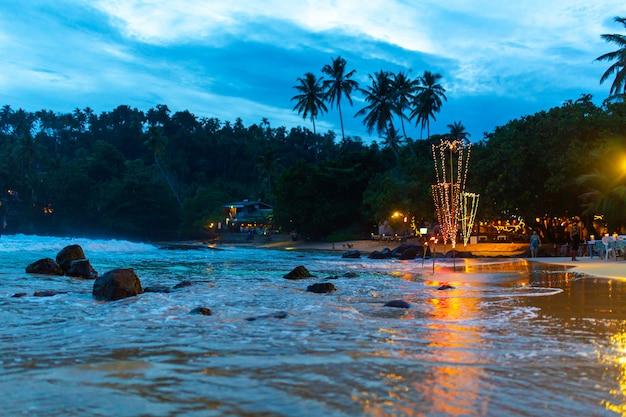 Restaurant aan de oceaan met verlichting en tafels op een zandstrand