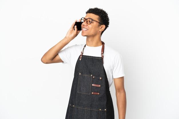 Restaurant afro-amerikaanse ober man geïsoleerd op een witte achtergrond die een gesprek voert met de mobiele telefoon